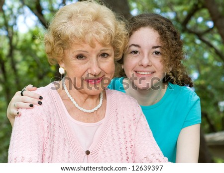 Portrait of a beautiful senior woman with her pretty teen granddaughter. - stock photo