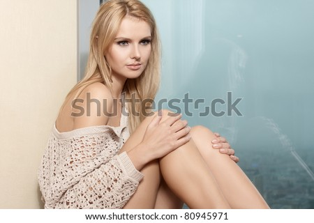 Portrait of a beautiful sensuality young woman with long blonde hair wearing a sweater - stock photo