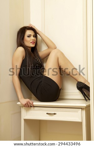 Portrait of a beautiful sexy and attractive young adult sensuality pretty brunette woman posing in black dress in retro style luxury apartment - stock photo