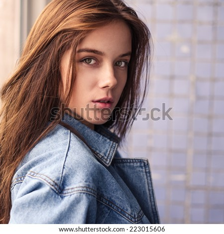 portrait of a beautiful sexy blonde in a denim jacket at home - stock photo