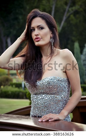 portrait of a beautiful sexy brunette in an elegant dress outdoors