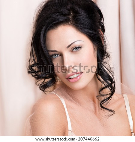 Portrait of a beautiful sexy tender woman with creative hairstyle. Model posing at studio