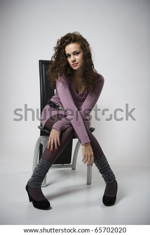 Portrait of a beautiful sexy woman sitting on a chair  over gray background - stock photo