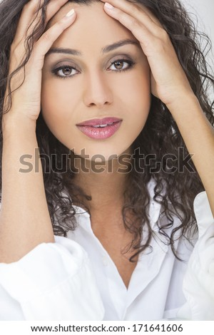 Portrait of a beautiful sexy young mixed race woman or girl with hands on her face wearing a white shirt - stock photo