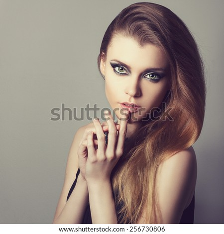 Portrait of a beautiful sexy young woman with perfect skin and make-up closeup. Emotional photo in studio. Hand near lips