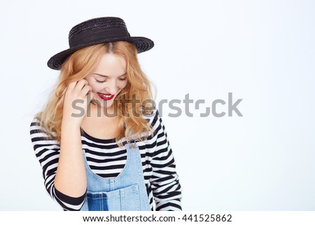 Portrait of a beautiful shy young brunette girl isolated on white background with copyspace Young woman in stylish hat and denim with eyes closed - stock photo