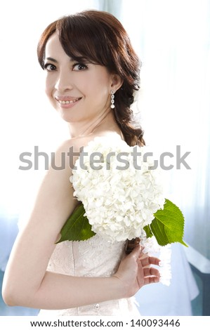 Portrait of a beautiful smile woman with bouquet of white flower - stock photo