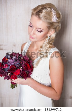 Portrait of a beautiful smiling blonde bride with wedding bouquet in hands