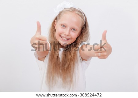 Portrait of a beautiful smiling girl showing thumbs up on white background - stock photo