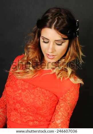 portrait of a beautiful smiling latin girl wearing a bright coral dress looking down and showing her perfect eyes make up - stock photo