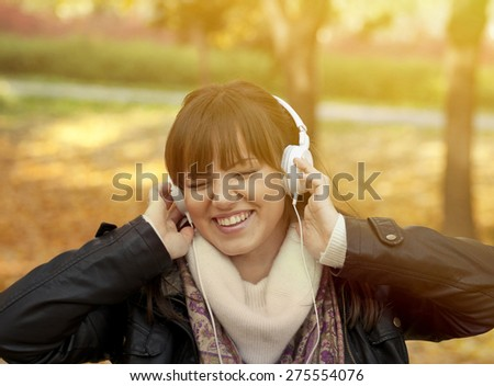 Portrait of a beautiful smiling woman listening to music and dancing - stock photo
