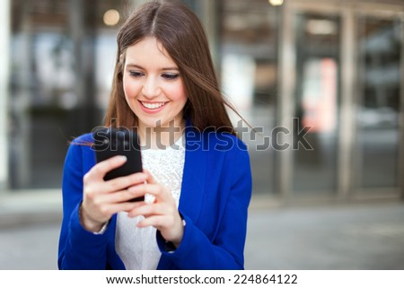 Portrait of a beautiful smiling woman using a mobile phone outdoors - stock photo
