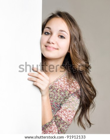 Portrait of a beautiful smiling young brunette girl with blank white sign. - stock photo