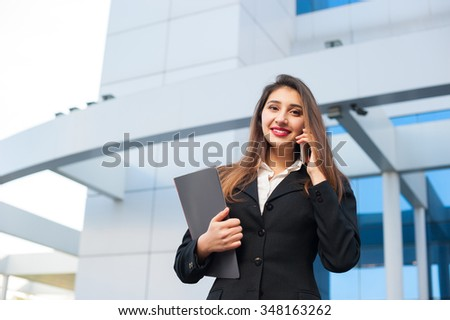 Portrait of a beautiful smiling young business woman with cell phone (mobile). Modern building as background. - stock photo