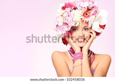Portrait of a beautiful spring girl wearing flowers hat. Studio shot. - stock photo