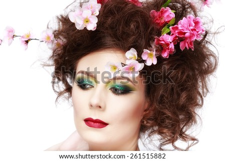 Portrait of a beautiful spring girl wearing flowers in hair. Studio shot