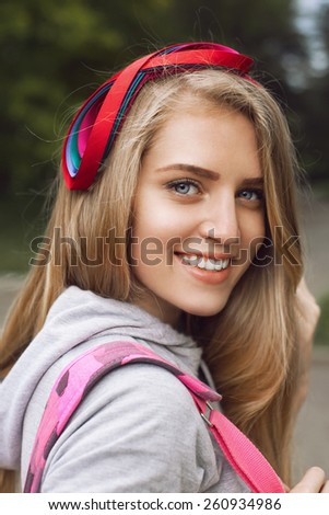 Portrait of a beautiful student walking through the park with a pink backpack. A girl wearing a bright beautiful hoop in the form of a bow - stock photo