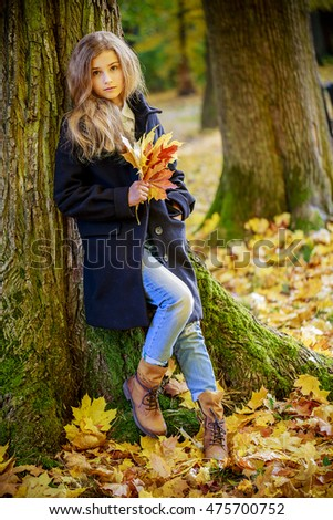 Portrait of a beautiful teenage girl with long hair in autumn park.
