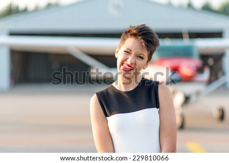 Portrait of a beautiful teenager making a funny face with an airplane as background