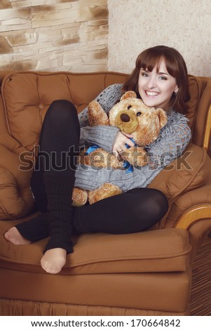 portrait of a beautiful tender girl sitting in the chair with teddy bear