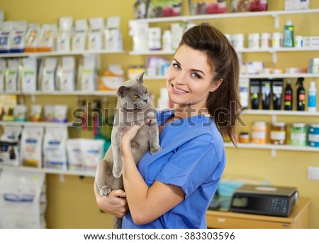 Portrait of a beautiful veterinarian holding young cat at clinic. - stock photo