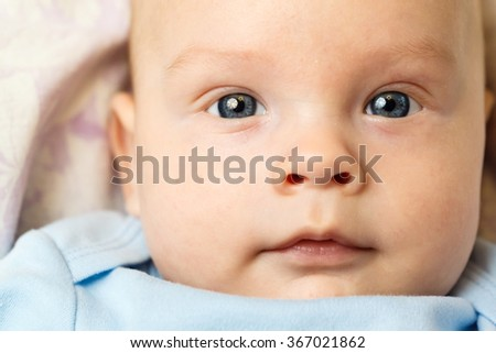Portrait of a beautiful white blue-eyed newborn baby close up