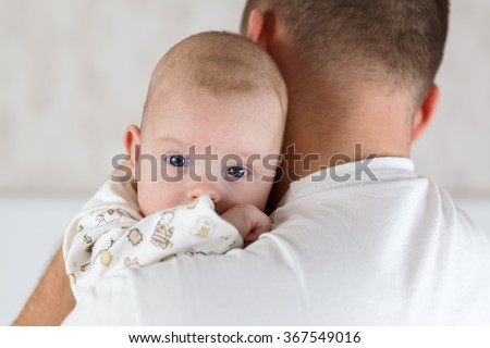 Portrait of a beautiful white blue-eyed newborn baby in the hands of Dad close up - stock photo