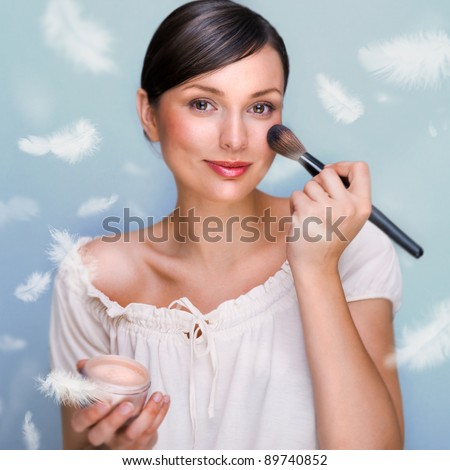 Portrait of a Beautiful woman applying makeup with brush on her face looking at camera and smiling against grey background. Feathers falls around her. Soft tender skin concept - stock photo