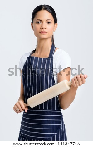 Portrait of a beautiful woman baker with a serious expression, holding a rolling pin - stock photo