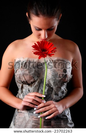 portrait of a beautiful woman covered in newspaper with flower