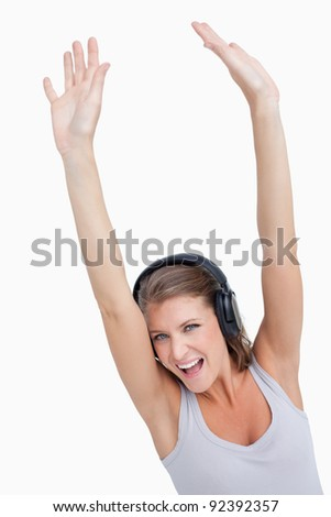 Portrait of a beautiful woman dancing while listening to music against a white background