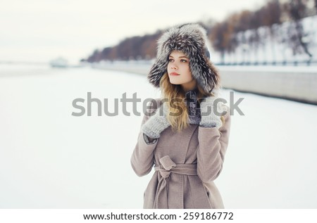 Portrait of a beautiful woman dressed a coat and fur hat in the winter field - stock photo