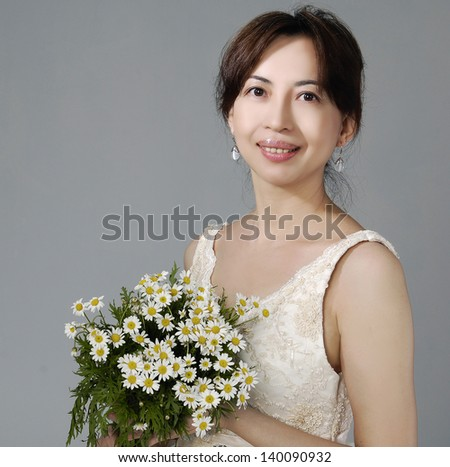 Portrait of a beautiful woman dressed as a bride with bouquet of flowers on gray - stock photo