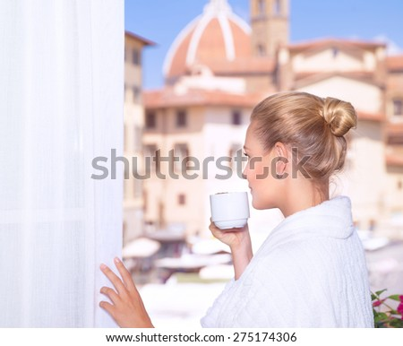 Portrait of a beautiful woman drinking coffee on the balcony and enjoying amazing European architecture, Italy, Florence - stock photo