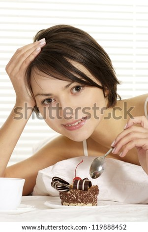 portrait of a beautiful woman eating cake on a white bed