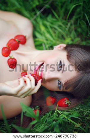 portrait of a beautiful woman eating strawberries in the park. - stock photo