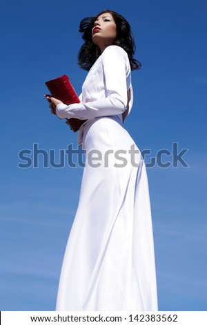 Portrait of a beautiful woman (fashion model) posing in elegant white atlas cocktail dress with red leather clutch in her hands over blue sky background. Outdoor shot - stock photo