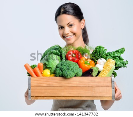 Portrait of a beautiful woman holding a wooden crate full of fresh raw organic produce vegetables - stock photo