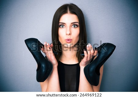 Portrait of a beautiful woman holding shoes. Wearing in sexy black dress. Looking at camera. - stock photo