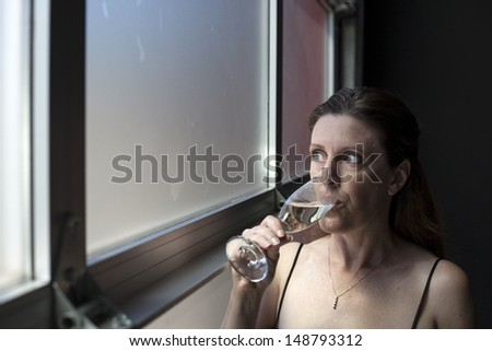 Portrait of a beautiful woman in a black dress with Champagne. - stock photo