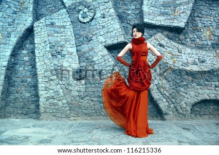 portrait of a beautiful woman in a red dress - stock photo