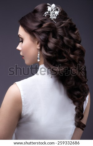 Portrait of a beautiful woman in a wedding dress in the image of the bride. Picture taken in the studio on a grey background.Hairstyle back view