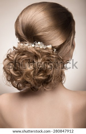 Portrait of a beautiful woman in a wedding dress in the image of the bride. Picture taken in the studio on a grey background. hairstyle the back