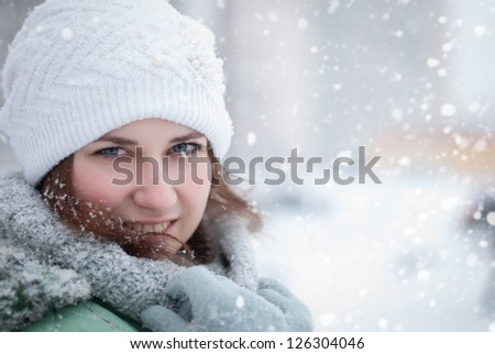 Portrait of a beautiful woman in a white hat in the snow.