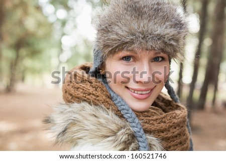 Portrait of a beautiful woman in fur hat with woolen scarf in the woods - stock photo