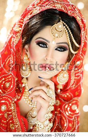 Portrait of a beautiful woman in glamorous outfit and jewellery with makeup - stock photo