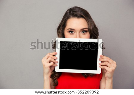 Portrait of a beautiful woman in red dress showig blank tablet computer screen over gray background - stock photo