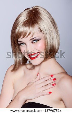 portrait of a beautiful woman in short blond bob with bright make-up on studio background - stock photo