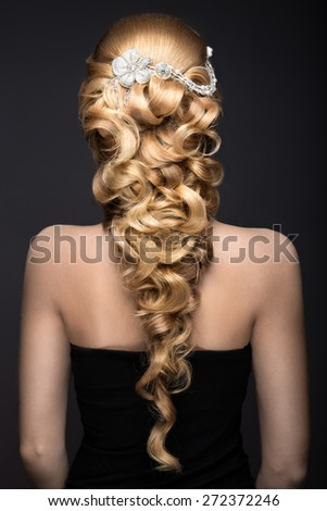 Portrait of a beautiful woman in the image of the bride with lace in her hair. Picture taken in the studio on a grey background. Beauty face. wedding hairstyle back view - stock photo