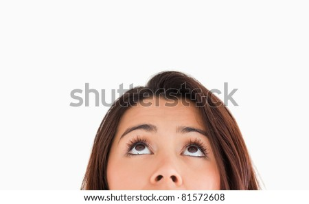 Portrait of a beautiful woman looking up while standing against a white background - stock photo